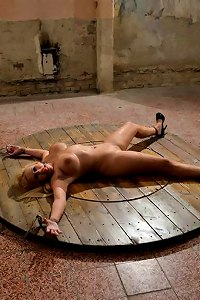 Classic BDSM wheel with a fully nude woman spread-bound on top of it: helpless and manhandled  Submissed