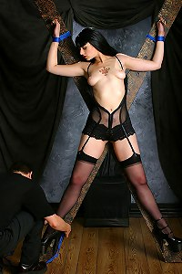 Hot brunette in sexy wear restrained in a spreadeagle position