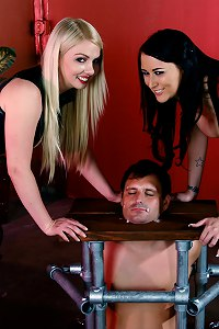 Mistresses Alexis Grace and Lexi Sindel humiliate their caged and chastised slave bitch by spitting all over his helpless face.
