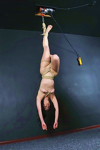Cute brunette amateur is tied up tightly with ropes and then suspended from the ceiling