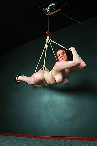 Master ties amateur red haired babe firmly and then hoist her up to the ceiling in suspension bondage.